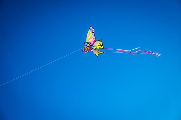 Volo variopinto dell'aquilone nel cielo blu, spazio negativo per la copia.