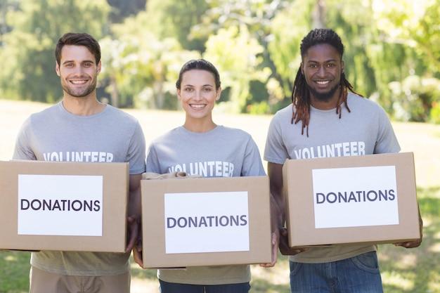 Volontari felici con le scatole di donazione in parco