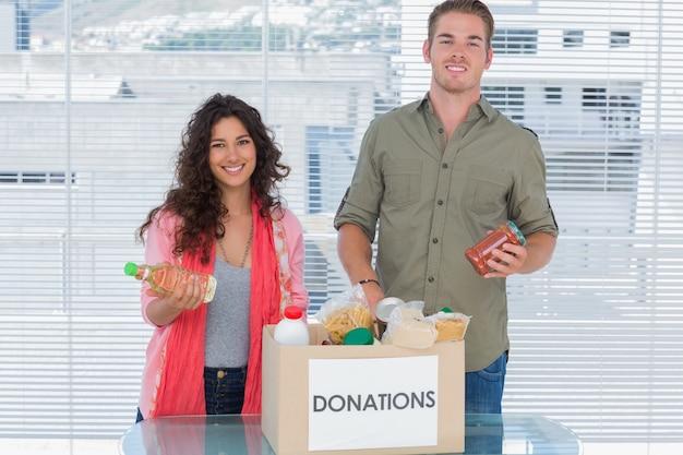 Volontari sorridenti che prelevano cibo dalla scatola delle donazioni