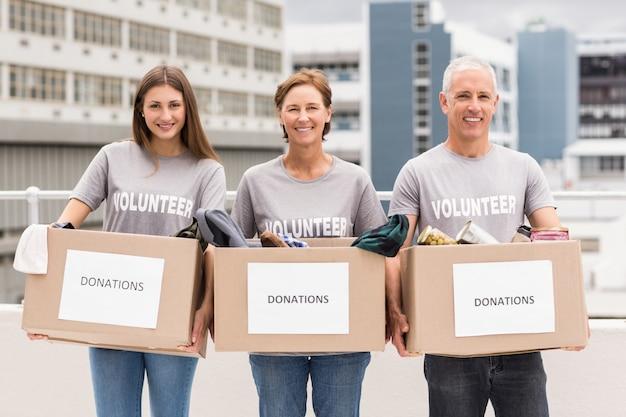Volontari sorridenti che tengono le scatole di donazione