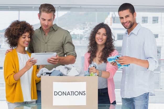 Volontari sorridenti che usano la tavoletta e tirano fuori vestiti dalle donazioni