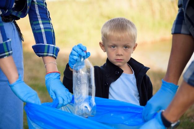 Volontariato, beneficenza, concetto di persone ed ecologia, volontari che usano il sacco della spazzatura mentre raccolgono rifiuti