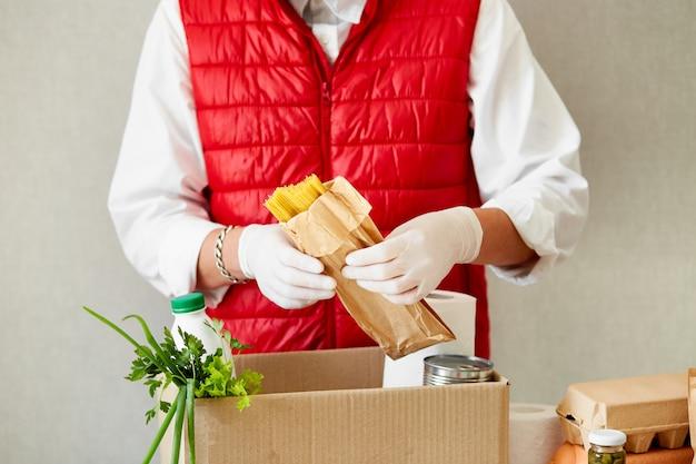 Volontariato con guanti chirurgici mettendo cibo nella scatola delle donazioni