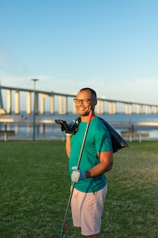 Volontario maschio felice che posa nel parco della città