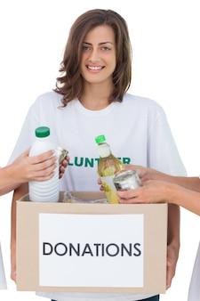 Volontario sorridente che tiene una scatola di donazione di cibo