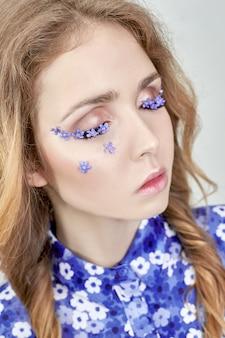 Volto di donna con fiori blu, la ragazza in fiore