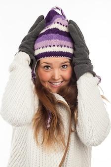 Volto di donna graziosa con guanti e berretto invernale a maglia con sorriso