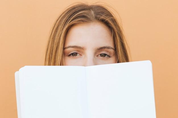 Volto di giovane donna bionda con il libro bianco sulla bocca
