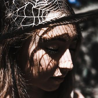 Volto di giovane donna in cappello da strega chiudendo gli occhi