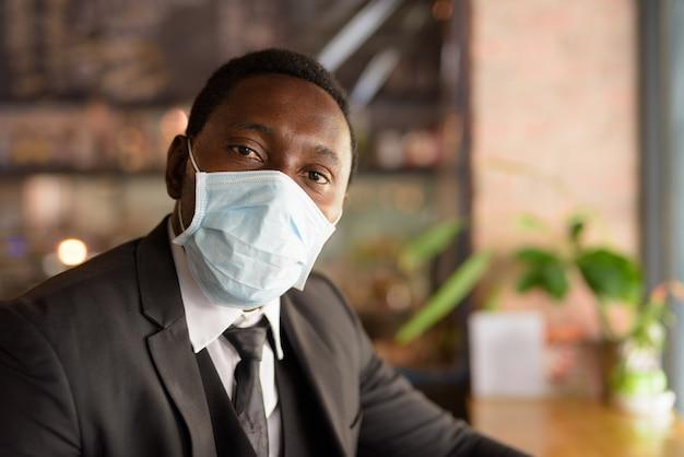 Volto di uomo d'affari africano che indossa la maschera per la protezione dallo scoppio del virus corona all'interno della caffetteria come la nuova normalità