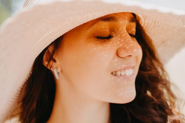 Volto femminile in un cappello facciale in un cappello, dalla luce del sole una donna ha un'ombra sul viso