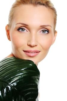 Volto sano di una donna caucasica con foglia verde