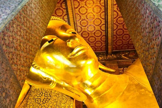 Volto statua di buddha in oro reclinabile. wat pho, bangkok, tailandia