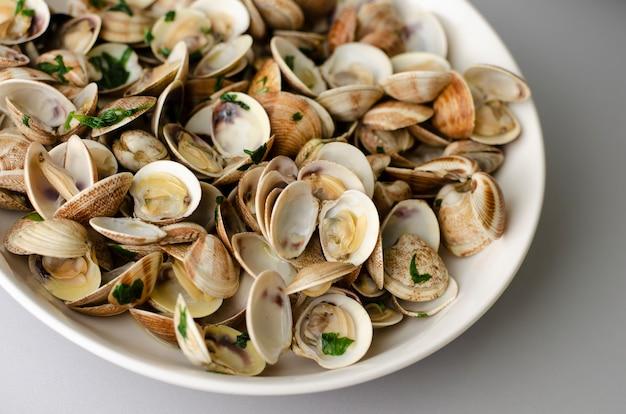 Vongole al vapore in salsa di aglio in una ciotola bianca. avvicinamento