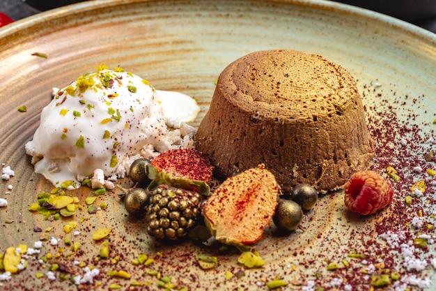 Vulcano color cioccolato dorato servito con gelato alla vaniglia e frutti di bosco