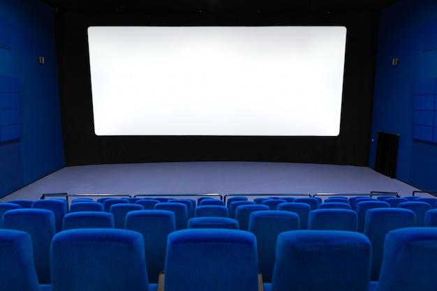 Vuoto del cinema in colore blu con schermo bianco bianco.