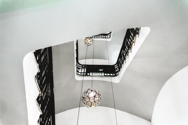 Vuoto di una scala interna di un vecchio edificio con pareti bianche e ringhiera nera.
