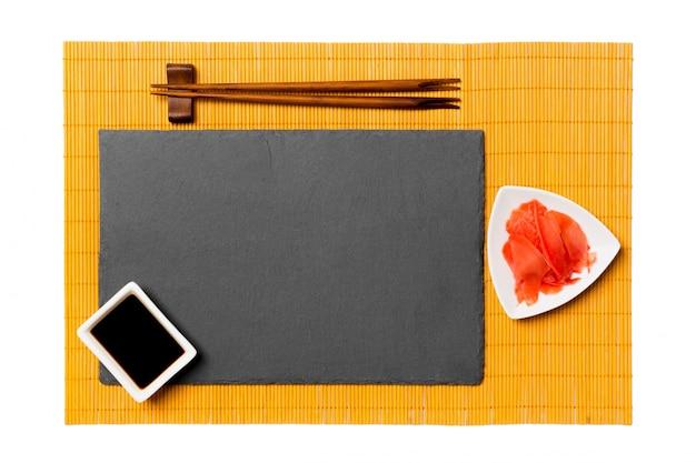 Vuoto piatto rettangolare in ardesia nera con le bacchette per sushi, zenzero e salsa di soia sul tappetino di bambù giallo