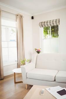 Vuoto soggiorno con divano e tavolo con giornale e televisione a distanza
