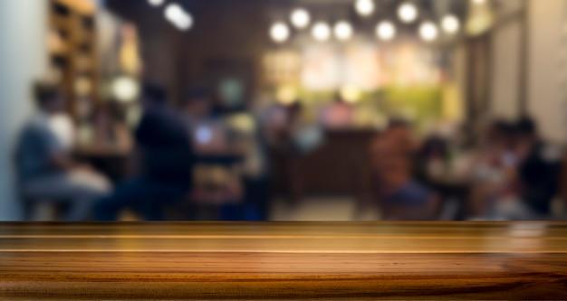 Vuoto tavolo di legno per il prodotto presente sul negozio di caffè o soft drink sfocatura sfondo bar con immagine bokeh.