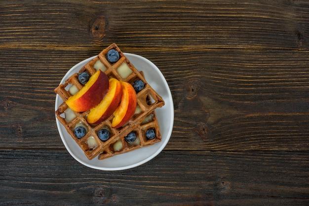 Waffle belgi al cioccolato con frutti e bacche. deliziosa colazione di legno. vista dall'alto, copyspace