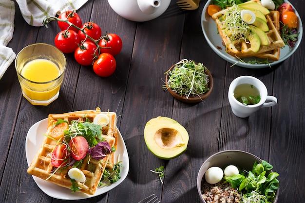 Waffle belgi con avocado, uova, micro verde e pomodori con succo d'arancia e tè sul tavolo di legno. colazione perfetta per cibi sani o dimagrire. panino con avocado.