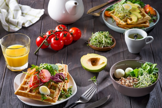 Waffle belgi con avocado, uova, micro verde e pomodori con succo d'arancia e tè sul tavolo di legno