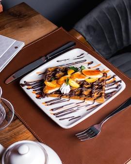 Waffle belgi con fettine di banana, kumquat, panna e cioccolato