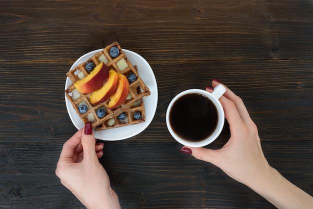 Waffle belgi con frutta e bacche. mano femminile con una tazza di caffè. sfondo di legno vista dall'alto
