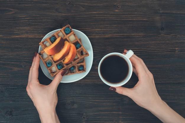 Waffle belgi con frutta e bacche. mano femminile con una tazza di caffè. sfondo in legno vista dall'alto