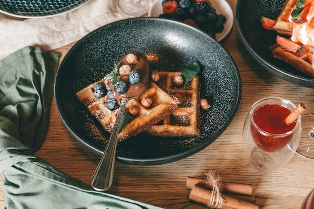 Waffle belgi con frutti di bosco, gelato e cioccolato. impostazione del tavolo per la colazione. stile di vita mattutino.