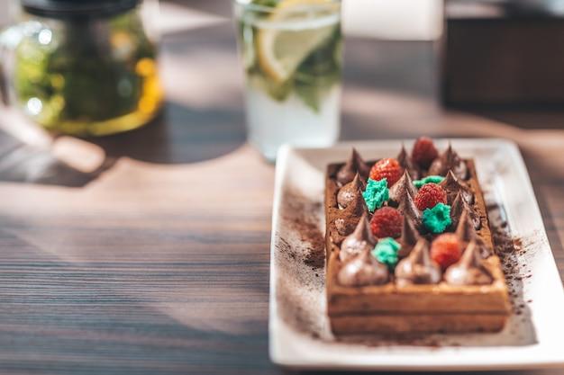 Waffle belgi con lamponi, serviti con teiera e bicchiere di limonata sul tavolo di legno.