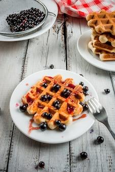 Waffle belgi e bacche estive e barattolo di ribes