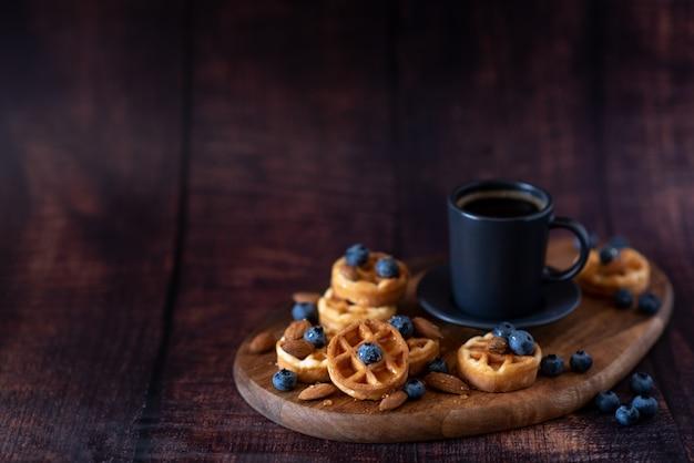 Waffle belgi fatti in casa, tazza di caffè in ceramica bianca, latte, cucchiaino e chicchi di caffè.
