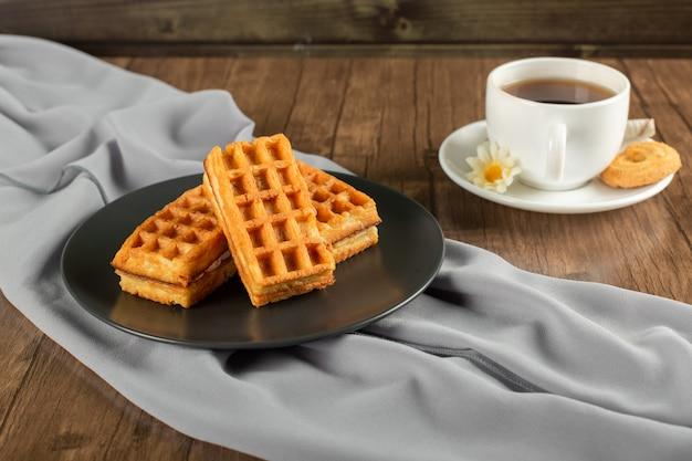 Waffle belgi in un piatto nero e una tazza di tè