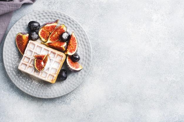 Waffle belgi tradizionali con uva e fichi di zucchero a velo. accogliente colazione fatta in casa. sfondo grigio cemento. copia spazio.