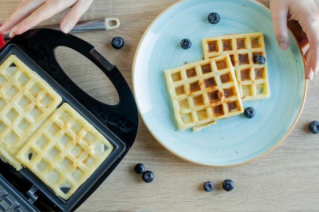 Waffle che vengono cotti nella macchina per waffle. cialde salate. concetto di colazione.