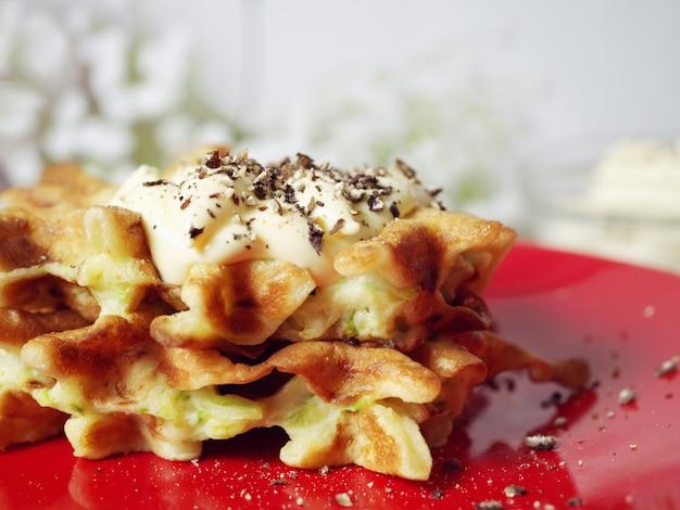 Waffle di zucchine su un piatto rosso con salsa e spezie