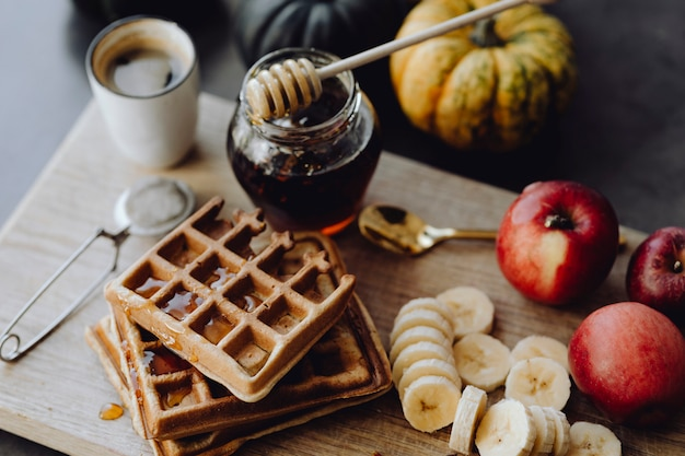 Waffle e fette di banana su un vassoio di legno accanto a un barattolo di miele
