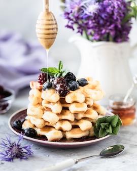 Waffle fatti in casa con frutti di bosco e miele, una tazza di caffè sul tavolo con un mazzo di lillà