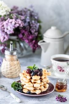 Waffle fatti in casa con frutti di bosco e miele, una tazza di caffè sul tavolo con un mazzo di lillà.
