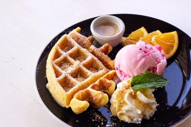 Waffle fatti in casa serviti con gelato alla fragola. dessert dolce