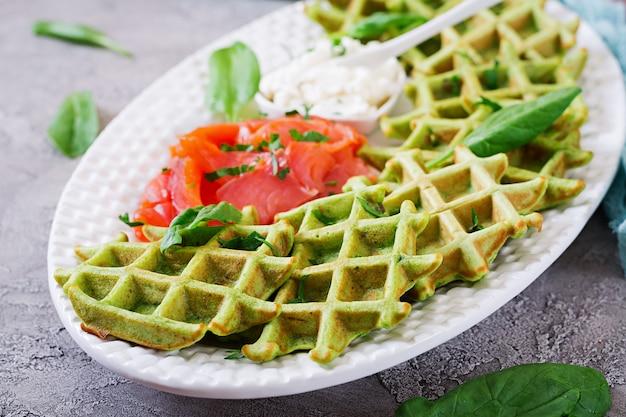 Waffle salati con spinaci e crema di formaggio, salmone in zolla bianca. cibo gustoso.