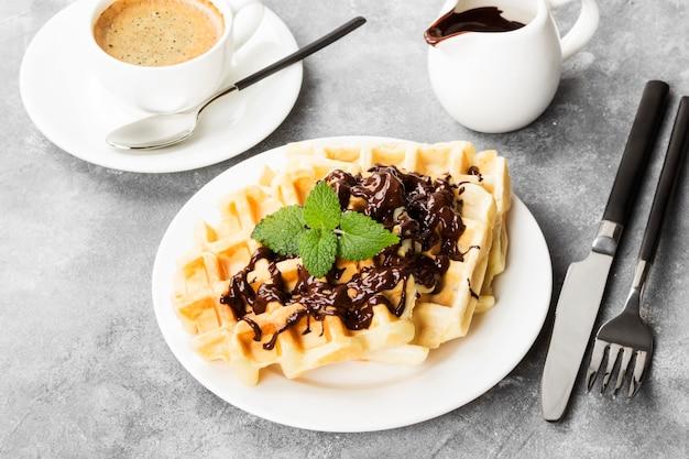 Waffle sul piatto bianco con cioccolato e menta, caffè, salsiera con cioccolato