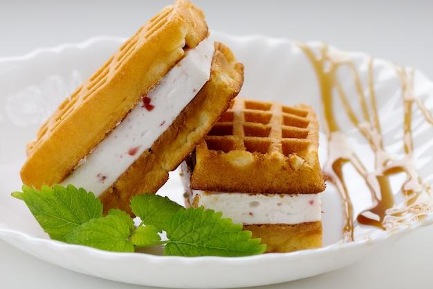Waffle viennesi con soufflé, pezzi di fragola, caramello e menta su un piatto bianco
