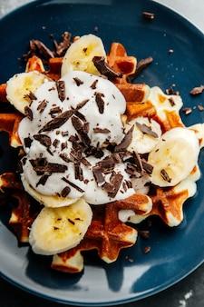 Waffle viennesi su un piatto, con una mollica di cioccolato e fette di banana