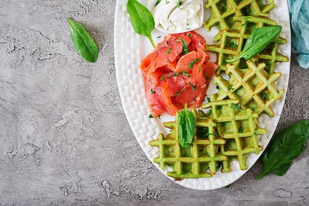 Waffles salati con spinaci e crema di formaggio, salmone in piatto bianco. cibo gustoso.