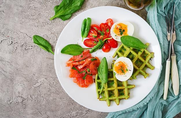 Waffles salati con spinaci e uova, pomodoro, salmone in piatto bianco.