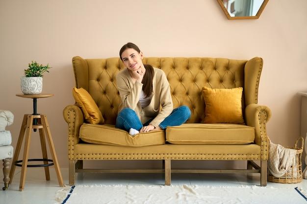 Weekend di umore calmo. donna sul divano rilassante in salotto, pensando e ricordando momenti piacevoli