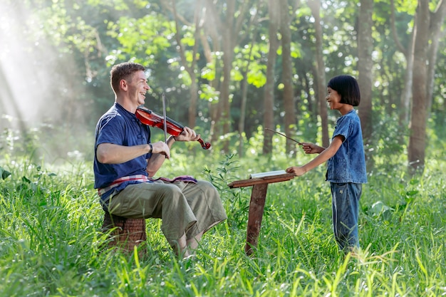 Western uomo che suona il violino con ragazze tailandesi